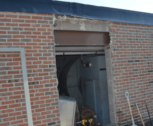 PHOTO 7: A low roof structural beam at the head of the door was prepped, primed and painted at SD 113 Deerfield High School.