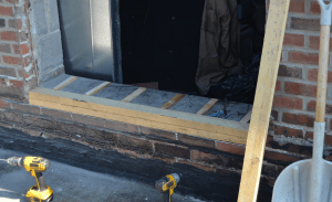 PHOTO 8: Here the door sill is being raised with wood blocking at SD 113 Deerfield High School. Because the brick was offset with the interior CMU, two layers of wood were installed at the exterior and one layer of shimmed wood will be installed on the interior. The interior sill will be covered with membrane, followed by prefinished metal and door sill.