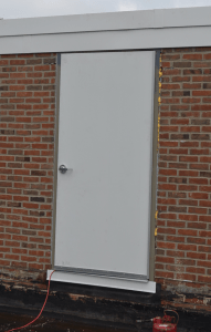"""PHOTO 9: The new hollow metal door and frame at SD 113 Deerfield High School. The sill was waterproofed and the membrane """"hung"""" to be tied into the new base flashing when the roof is installed. Only a vapor retarder is in place at this point."""