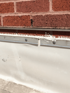 PHOTO 1: The through-wall flashing stainless-steel drip can be observed projecting nicely from the wall—but the termination of the roof base flashing more than 1-inch below resulted in a section of the brick wall that allows water to pass into the wall below the through-wall flashing and behind the roof base flashing, resulting in the damage seen in Photo 2.