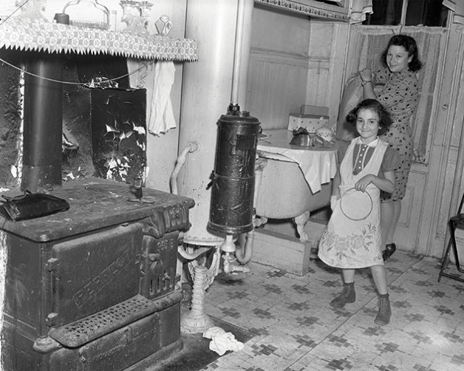 Family in tenement kitchen with coal burning stove (firebox on the right). The stand behind it is holding a galvanized iron water tank and the black unit on the side of the tank is a gas fired water heater with copper pipes inside. There was no safety or pilot system. This family moved to the Kingsborough Houses in Bedford-Stuyvesant in 1941.