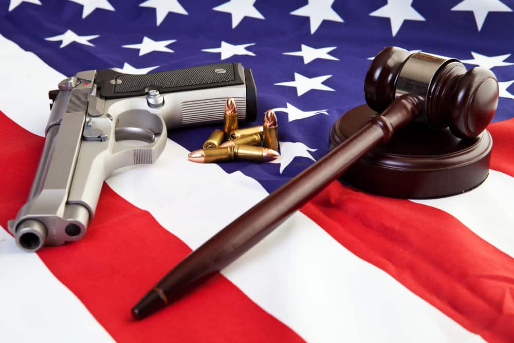 handgun, bullets, and a legal gavel on a US flag