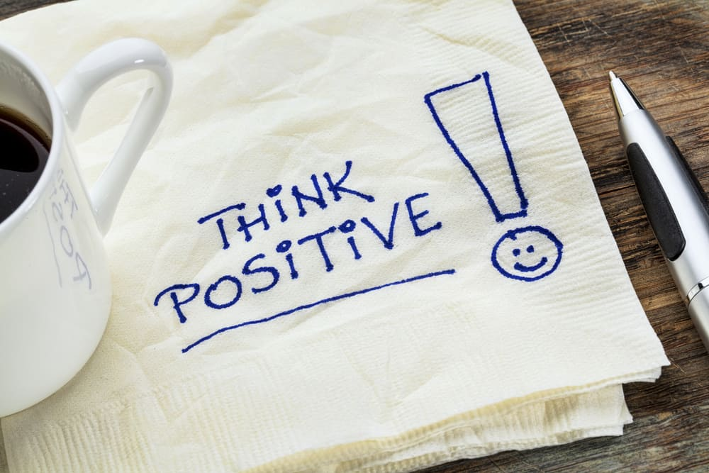 "Napkin with ""think positive!"" written on it. On top of the napkin is a mug of coffee and next ot the napkin is a pen."