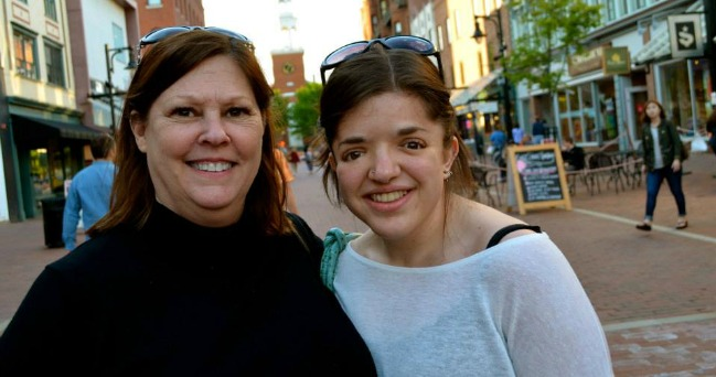 Photo of the author and her mother smiling for the camera, on a street in front of a restaurant.