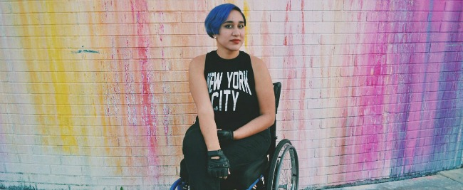 Photo of Annie Segarra with blue hair in a black outfit. Sitting in a wheelchair in front of a pastel rainbow splattered wall.
