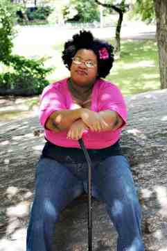 Outdoors, day time. Denarii, a proudly fat, brown-skinned Black woman, is wearing a pink flower in her afro, a black tank top with a pink half-sweater over it, and dark denim jeans. She's sitting on a large gray rock, resting her hands on her black cane. She's facing the camera, not smiling. In the background are the green trees and grass of Central Park.