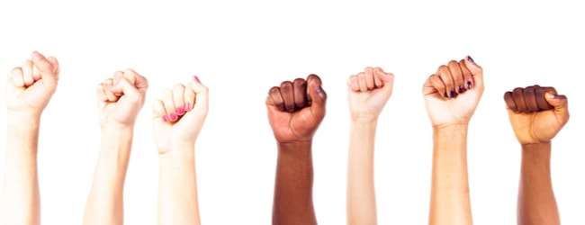 Fists of people of different skin colors raised together in the air.