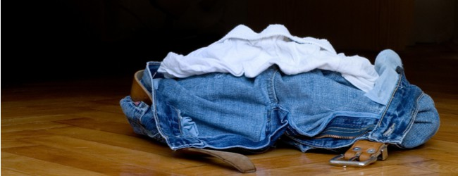 A pile of clothes - underwear, jeans, and a belt - on the floor.