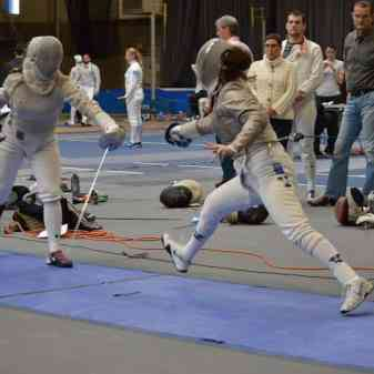A photo of Lillie Lainoff fencing at the Brandeis Invitational in 2016, where Yale went 5-0 and upset No. 8 St. John's in the process, 18-9. She is mid lunge, both her feet are off the ground.