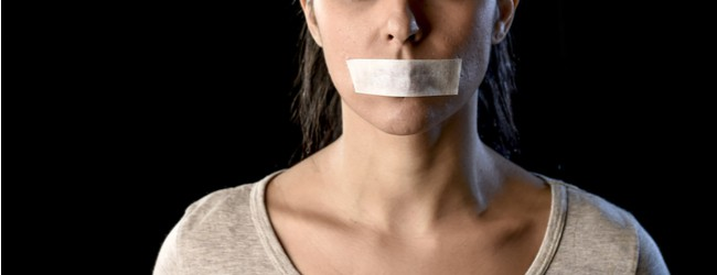 A female-presenting person shown from the nose to the neck, with duct tape over her mouth, indicating silence.