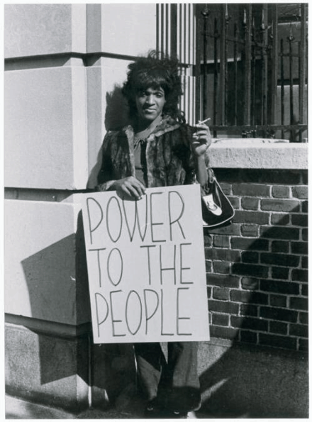 """Marsha P. Johnson, a Black trans woman, stands with a sign reading """"POWER TO THE PEOPLE."""" She is wearing a fur coat and holding a cigarette."""