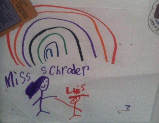 A child's drawing of a rainbow. Below the rainbow are two stick figures. One is Miss Scrader and one is Luis.