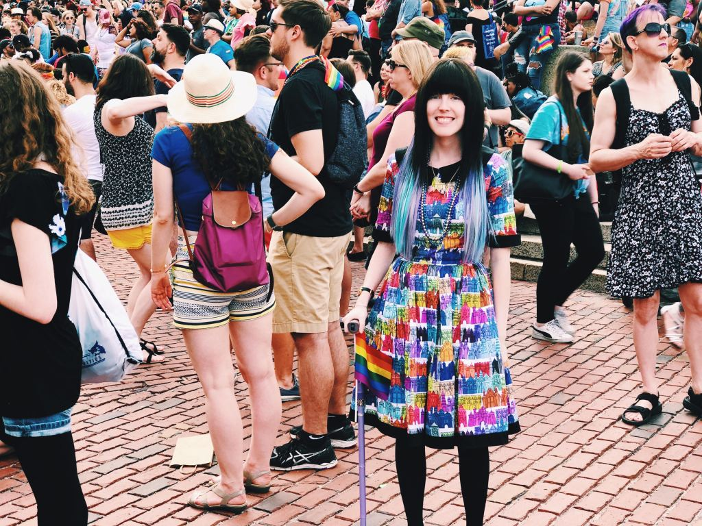 Alaina, a white thin femme person, standing in front of a crowd at Pride in Boston. She is wearing a dress with rainbow castles all over it. I have long hair that is dark brown on top and a mix of blues and purples on the bottom. She is standing with hert lavender cane with a rainbow flag attached to it, and smiling.
