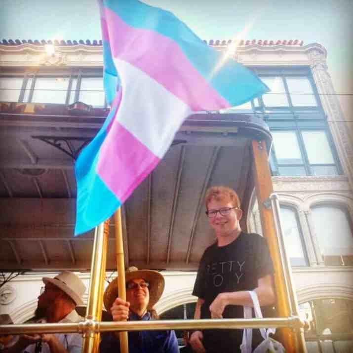Christian, a white trans man, is on a trolley. He is smiling. Next to him, someone is holding the Trans Pride flag.
