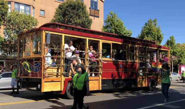 A trolley with people on it in rolling through a march.