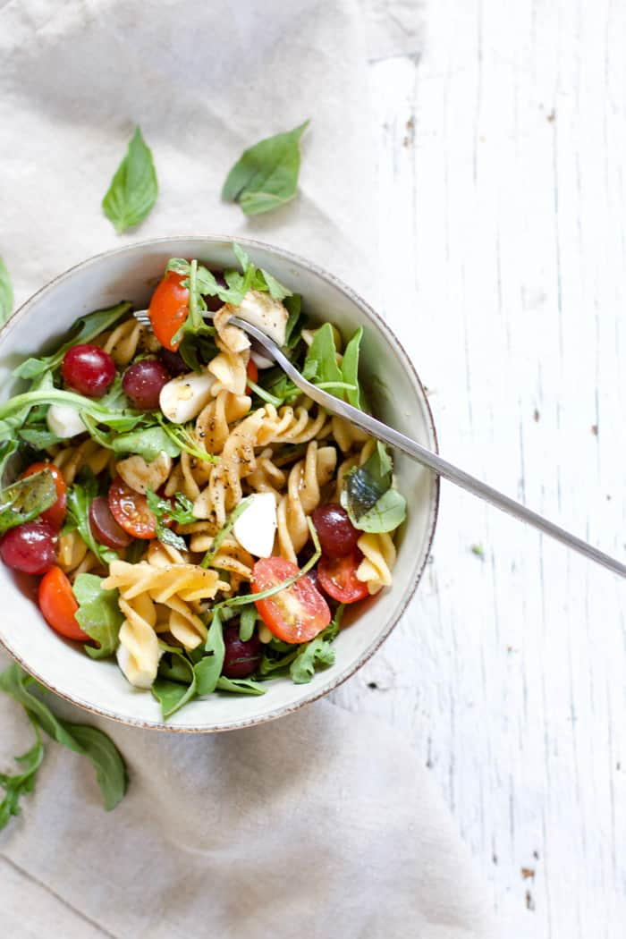 Fruity Caprese Pasta Salad - A fruity twist in the classic caprese salad! Summery, refreshing, perfect for picnics. Grapes, grape tomatoes, fresh mozzarrella, arugula, basil, olive oil & balsamic | rootsandradishes.com