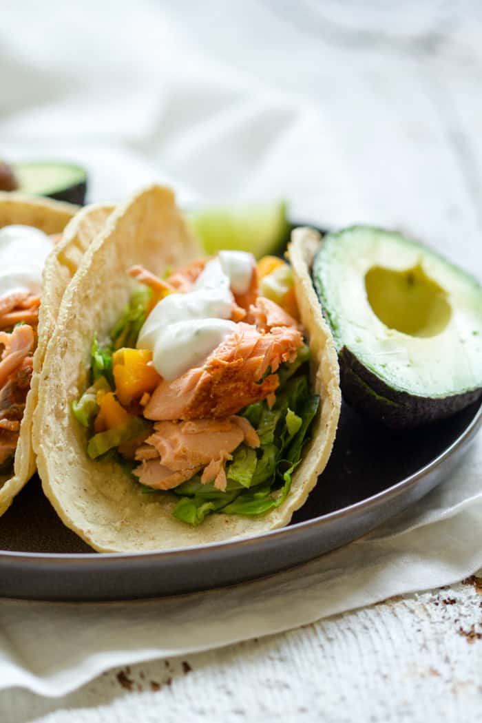 Smoky Salmon Butternut Squash Tacos - Complete with lime crema! So simple, healthy, and flavorful. Sometimes you just need an easy weeknight meal during the busy holiday season. These tacos are it! Wild-caught salmon, smoked paprika, butternut squash, Brussels sprouts, lime crema. Come and try it out! | rootsandradishes.com