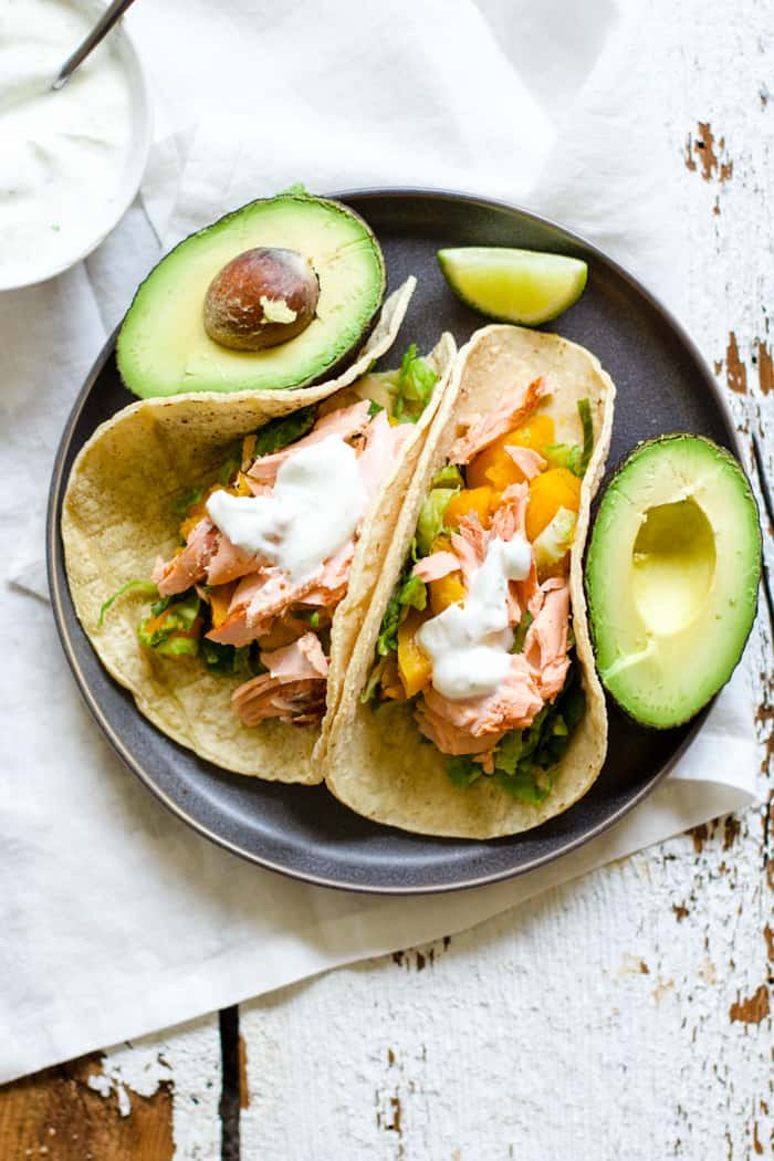 Smoky Salmon Butternut Tacos - Complete with lime crema! So simple, healthy, and flavorful. Sometimes you just need an easy weeknight meal during the busy holiday season. These tacos are it! Wild-caught salmon, smoked paprika, butternut squash, Brussels sprouts, lime crema. Come and try it out! | rootsandradishes.com