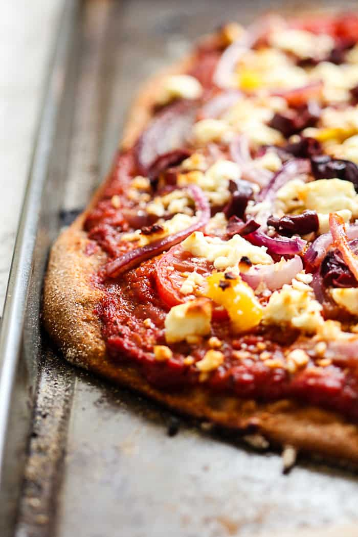 Fresh, homemade Greek pizza with whole wheat crust, roasted red pepper sauce, tomatoes, red onions, garlic, yellow peppers, kalamata olives, feta, and fresh oregano. Easy, healthy, comforting, delicious.   rootsandradishes.com