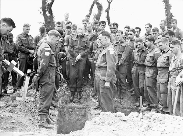 H Captain Callum Thompson, a Canadian chaplain, conducting a funeral service in the Normandy bridgehead, France, 16 July 1944.