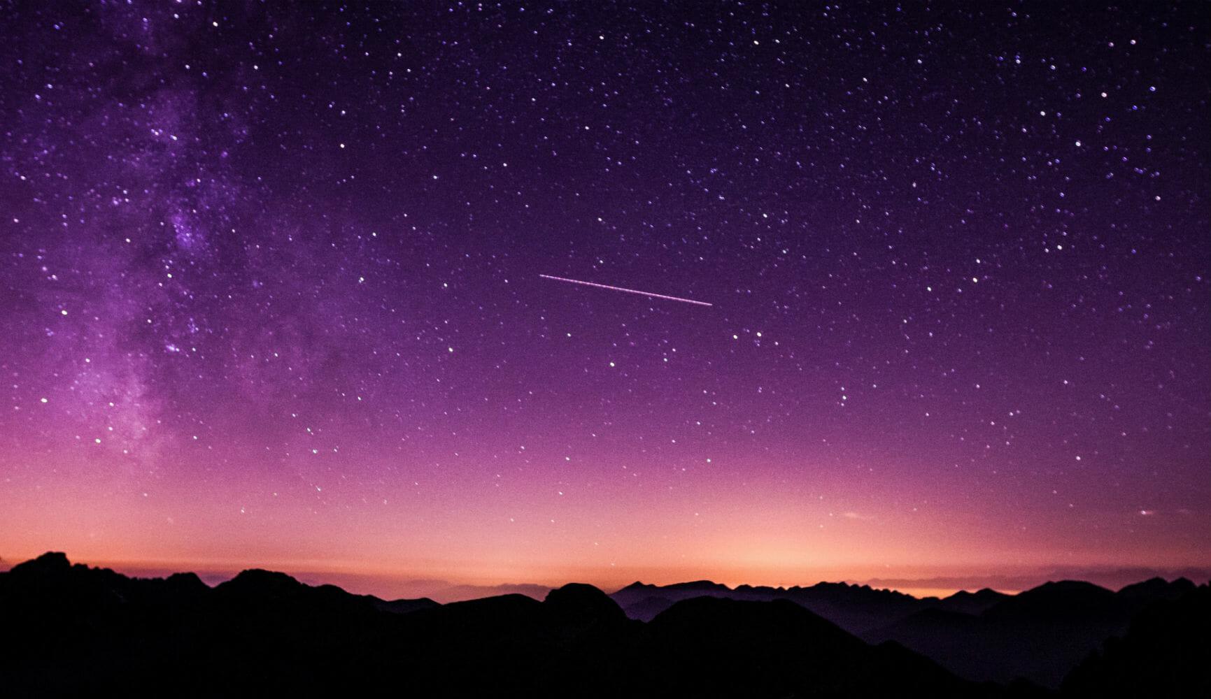 Cielo estrellado con estrella fugaz en el horizonte
