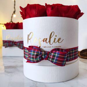 scatola toda bianca con rose rosse stabilizzate e nastro a motivo tartan di natale