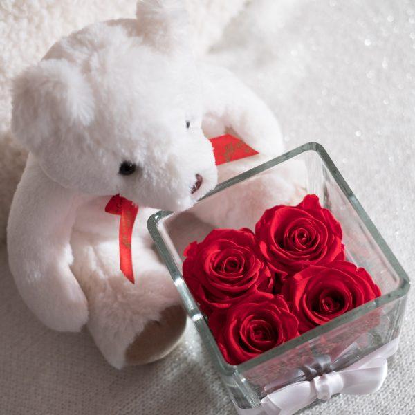 vaso di vetro con 4 rose stabilizzate di color rosso e nastro bianco attorno. Orsetto bianco vicino al vaso.