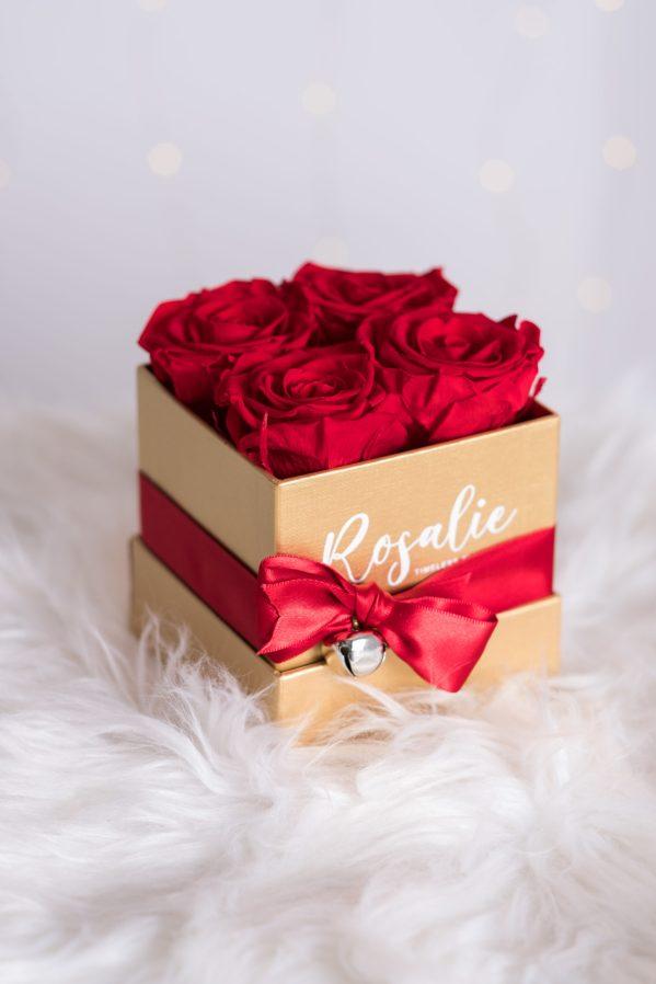 scatola dorata quadrata con 4 rose stabilizzate di color rosso e nastro rosso