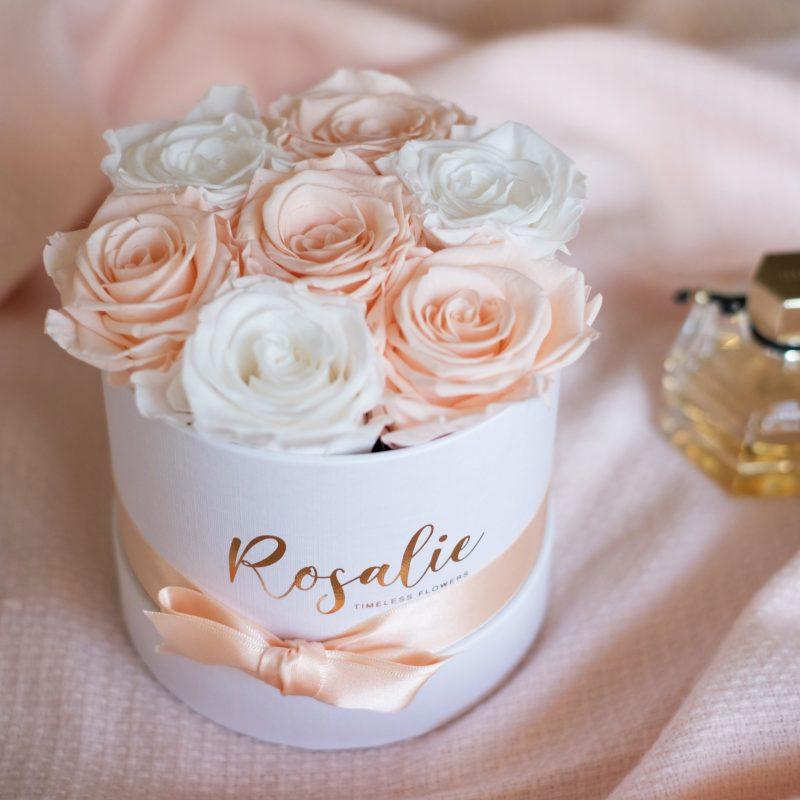 scatola tonda con 7 rose stabilizzate di cui 4 rosa porcellena e 3 bianche su tessuto rosa accanto ad un profumo