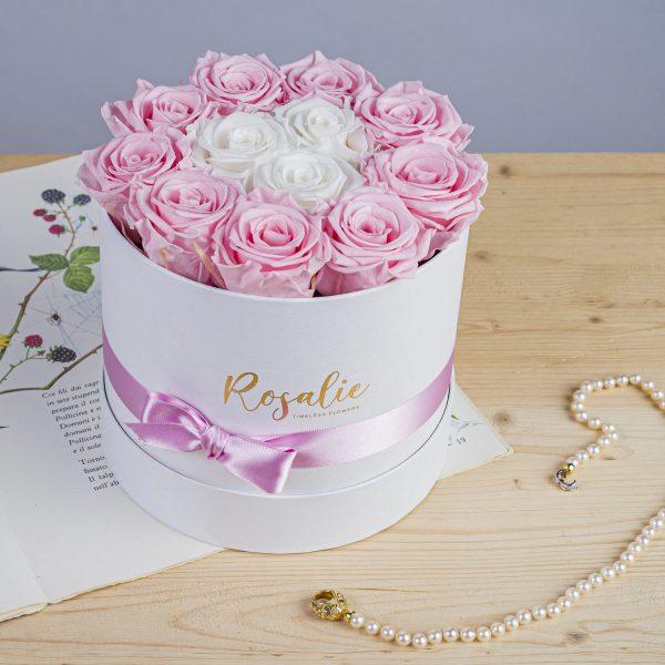 scatola da 12 rose stabilizzate di cui 9 di color rosa e 3 centrali bianche. Con nastro rosa attorno. Appoggiata su libro con accanto collana di perle. Su tavolo di legno chiaro.