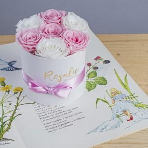 scatola da 7 rose stabilizzate di cui 4 di color rosa e 3 bianche vista a 45 gradi. Poggiata su libro di favole, su tavolo di legno chiaro.