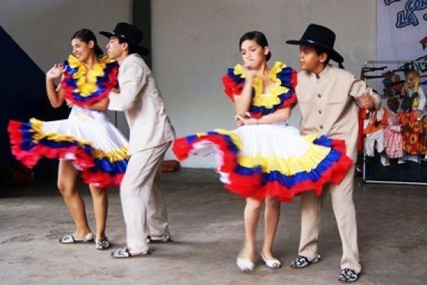 Parejas bailando joropo con sus trajes tradicionales.