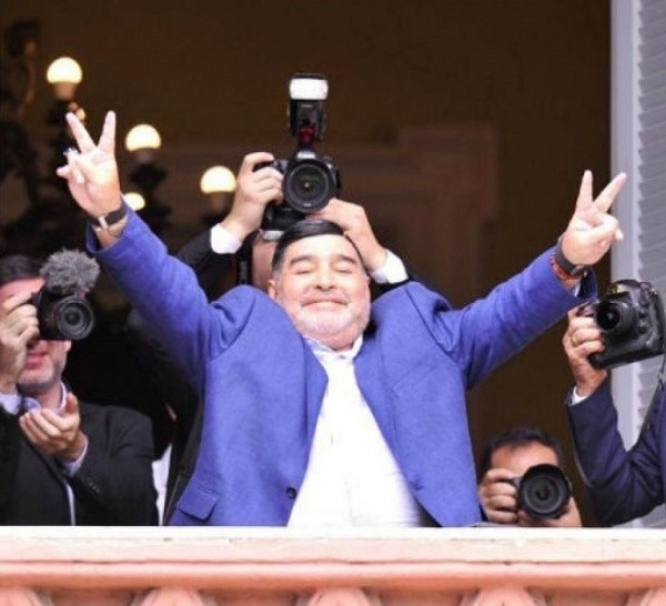 Diego en la Rosada con los dedos en V.