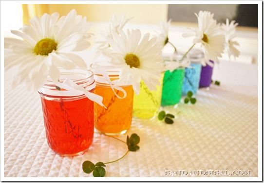 Rainbow Colored Water Mason Jar Centerpiece via Sand and Sisal | http://www.roseclearfield.com