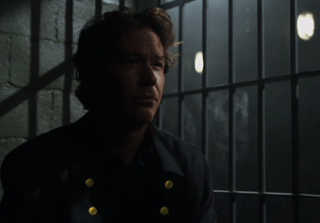 Nate in a jail cell with gold buttons photoshopped onto his coat to make him look like Javert
