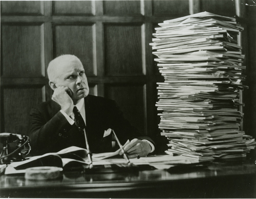 Man Looking at a Stack of Papers