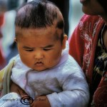 Uigar infant resembling the Happy Buddha sits in his mother's lap