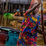 A young girl of Benin's Tofinu tribe poles her skiff filled with cargo