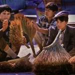 Uigar boys sell handmade brooms in Kashgar market