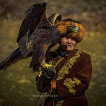 A Kyrgyz Eagle hunter dressed in traditional clothing and fox fur hat holds his champion Eagle