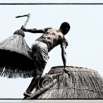 a Somba woman opens a granary by lifting the top off the hut