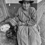 an old Peruvian woman sits in the market place selling her few potatoes