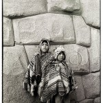 Two Peruvian boys dressed in traditional hand woven ponchos and hats stand by Incan stone work in Cuszco