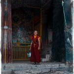 Tibet: A young monk poses in front of a Tanka