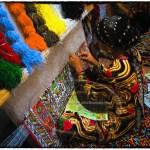 An Uzbek woman weaves an intricate patterned silk carpet