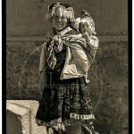 Peru: young woman in native garb carries her infant on her back