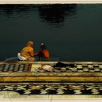 India: woman and boy by temple pool