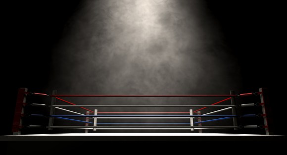 A regular boxing ring surrounded by ropes spotlit in the missle on an isolated dark background