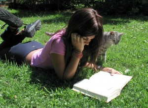 Young woman reding a book on a lawn