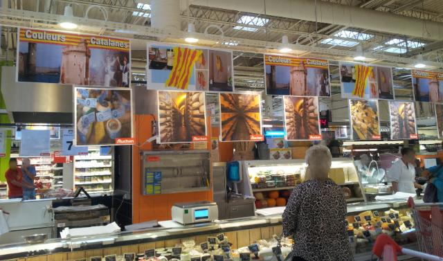 """Affiches au rayon fromage de Auchan Perpignan représentant Collioure, Le Castillet, des danseurs catalans, le pourou, et """"les Vigatanes"""" : tableau de Carole Alexandre, au rayon fromage de Auchan Perpignan"""